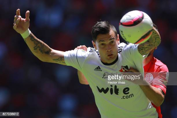 Milton Caraglio of Atlas struggles for the ball with Rodrigo Lopez of Toluca during the third round match between Toluca and Atlas as part of the...