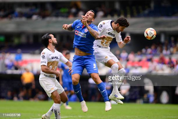 Milton Caraglio of Cruz Azul fights for the ball with Luis Quintana and Pablo Jaquez of Pumas during the 15th round match between Cruz Azul and Pumas...