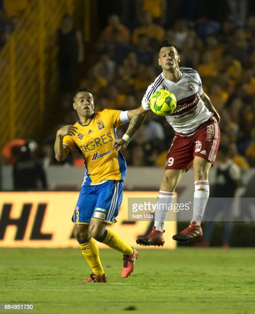 Milton Caraglio of Tijuana fights for the ball with Juninho of Tigres during the semi finals first leg match between Tigres UANL and Tijuana as part...