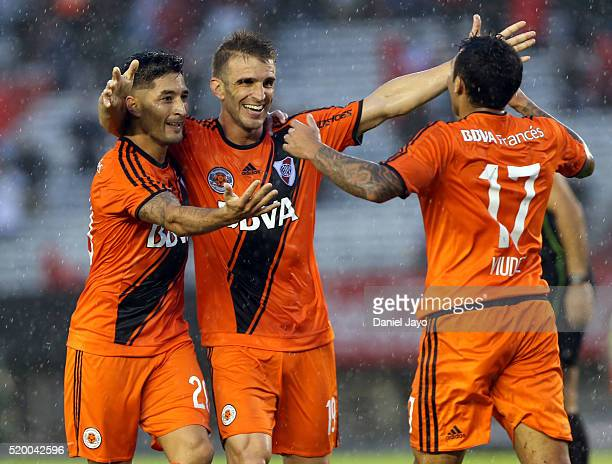 Milton Casco of River Plate celebrates with teammates Ivan Alonso and Tabare Viudez after scoring during a match between River Plate and Sarmiento as...
