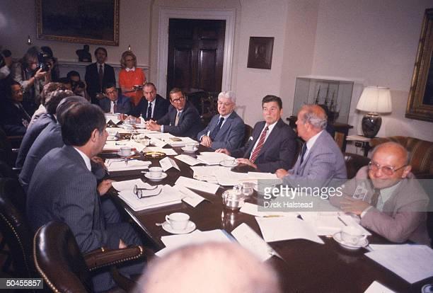 Milton Friedman, George Shultz, Pres. Ronald Reagan, Arthur Burns, William Simon, Walter Wriston & unknown at House Economy meeting w. Outside...
