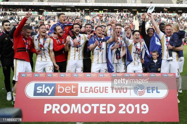 Milton Keynes player celebrate as they are promoted following their result in the Sky Bet League Two match between Milton Keynes Dons and Mansfield...