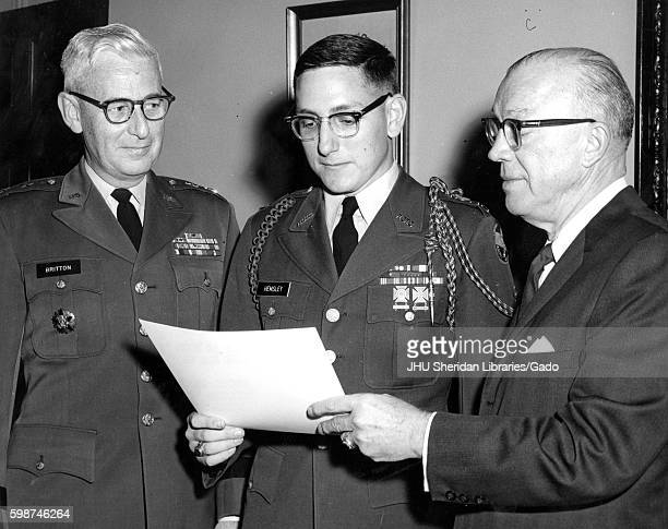 Milton Stover Eisenhower President of Johns Hopkins University stands to present the Distinguished Military Student Award to James Hemsley wearing...