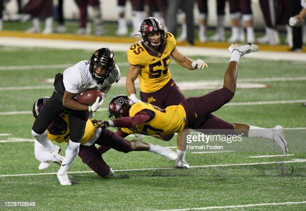 Milton Wright of the Purdue Boilermakers is tackled by Phillip Howard and Tyler Nubin of the Minnesota Golden Gophers during the fourth quarter of...
