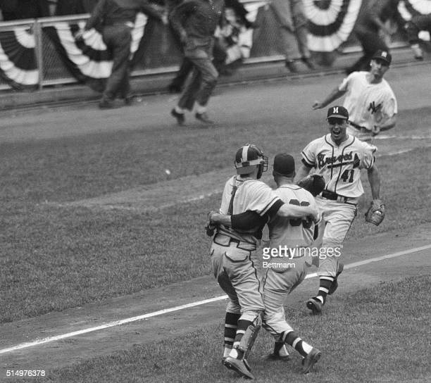 Milwaukee Brave's catcher Del Crandall hugs winning pitcher Lew Burdette as Ed Mathews runs in to join the celebration on the field here after they...
