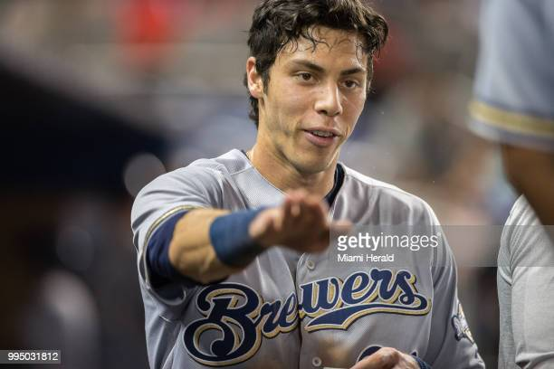 Milwaukee Brewers center fielder Christian Yelich talks to his coaches after scoring in the ninth inning to tie the game 33 at Marlins Park in Miami...