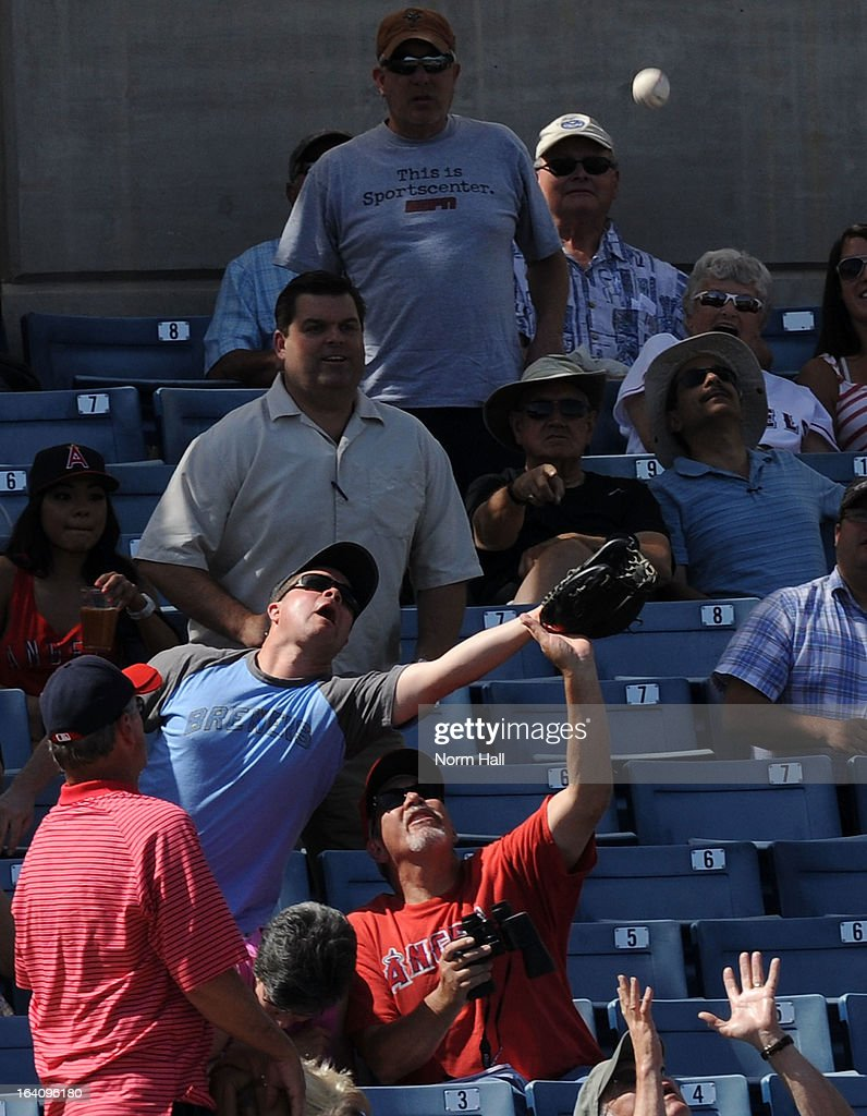A Milwaukee Brewers fan and Los Angeles Angels of Anaheim fan attempt to catch a foul ball at Maryvale Baseball Park against the Los Angeles Angels of Anaheim on March 19, 2013 in Maryvale, Arizona.