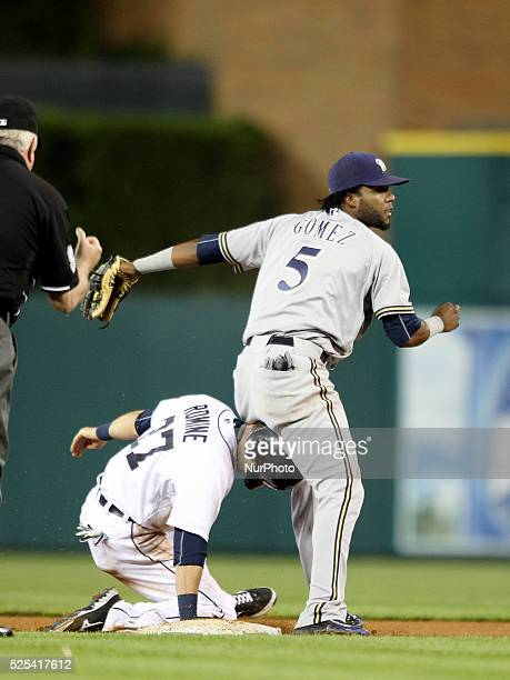 Milwaukee Brewers' Hector Gomez throws over Detroit Tigers' Andrew Romine after forcing him out at second base on the front end of a double play...