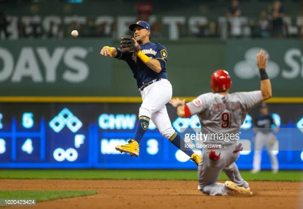 Milwaukee Brewers second baseman Hernan Perez turns a double play to end the game as Cincinnati Reds shortstop Jose Peraza tries to break up the play...