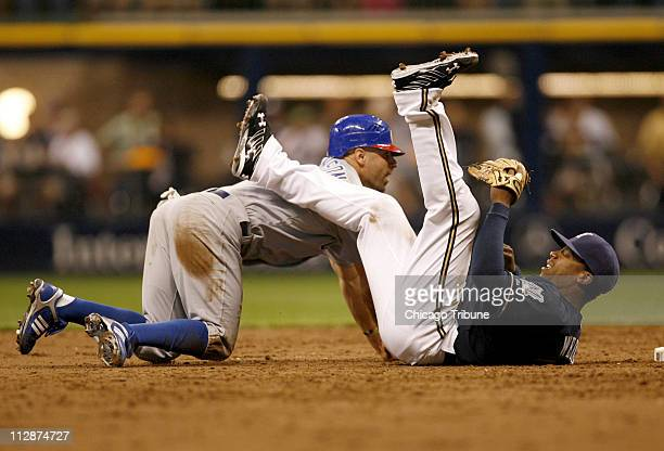 Milwaukee Brewers second baseman Rickie Weeks right is knocked to the ground and gets a throwing error to first base trying to complete a double play...