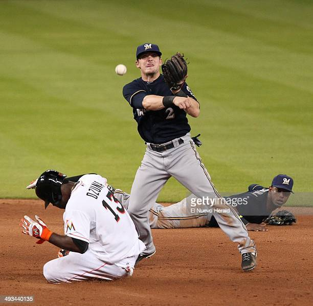Milwaukee Brewers shortstop Jean Segura throws to first base after getting the force out at second base on the Miami Marlins' Marcell Ozuna but was...