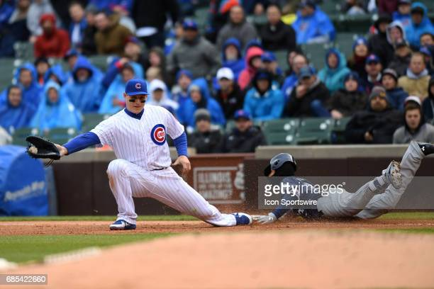 Milwaukee Brewers shortstop Orlando Arcia slides into firs base as Chicago Cubs first baseman Anthony Rizzo attempts a force out in the fourth inning...