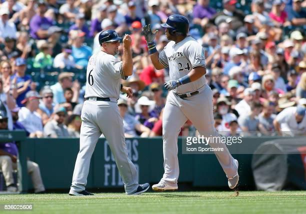 Milwaukee Brewers Third Base Coach Ed Sedar congratulates Brewers Infielder Jesus Aguilar as he rounds the bases following a solo homerun during a...