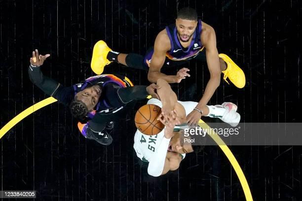 Milwaukee Bucks forward Giannis Antetokounmpo is fouled by Phoenix Suns forward Jae Crowder, left, as Phoenix Suns forward Mikal Bridges, right,...