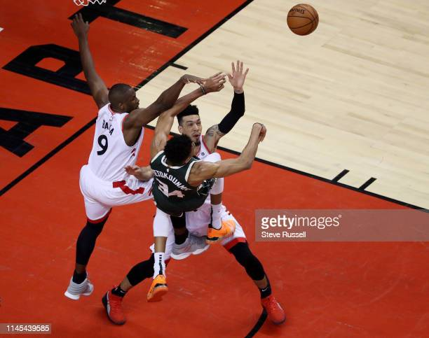 TORONTO ON MAY 21 Milwaukee Bucks forward Giannis Antetokounmpo passes the ball while being defended by Toronto Raptors center Serge Ibaka and...