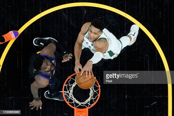 Milwaukee Bucks forward Giannis Antetokounmpo, right, dunks over Phoenix Suns center Deandre Ayton during the first half of Game Two of the NBA...