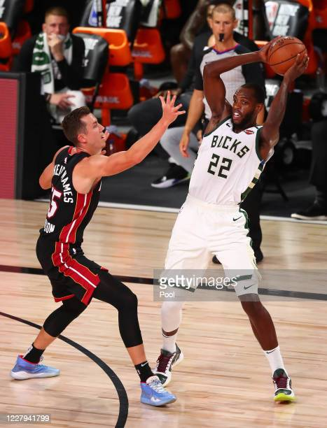 Milwaukee Bucks forward Khris Middleton controls the ball against Miami Heat guard Duncan Robinson during the first half of an NBA basketball game at...