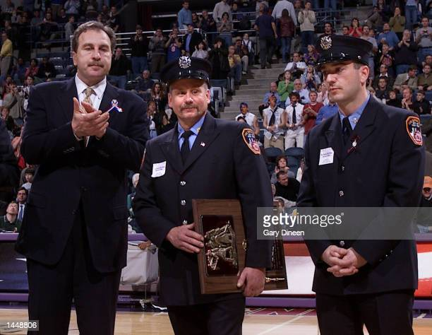 Milwaukee Bucks General Manager Ernie Grunfeld applauds as New York Firefighters Greg Fogan and Dan Baron are introduced during a halftime check...