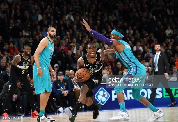 Milwaukee Bucks guard Eric Bledsoe is challenged by Charlotte Hornets guard Devonte' Graham during the NBA basketball match between Milwaukee Bucks...