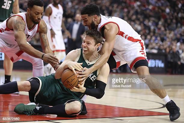Milwaukee Bucks guard Matthew Dellavedova holds onto the ball as Toronto Raptors guard Norman Powell and Toronto Raptors guard Cory Joseph try to...