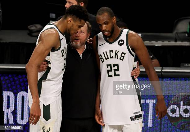 Milwaukee Bucks head coach Mike Budenholzer celebrates the win with Giannis Antetokounmpo and Khris Middleton after game seven of the Eastern...
