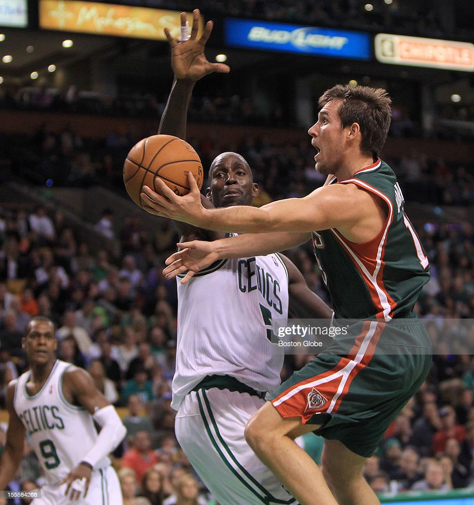 Milwaukee Bucks point guard Beno Udrih (#19) drives to the basket as Boston Celtics power forward Kevin Garnett (#5) defends during the fourth quarter as the Boston Celtics play the Milwaukee Bucks in their season home opener at TD Garden.