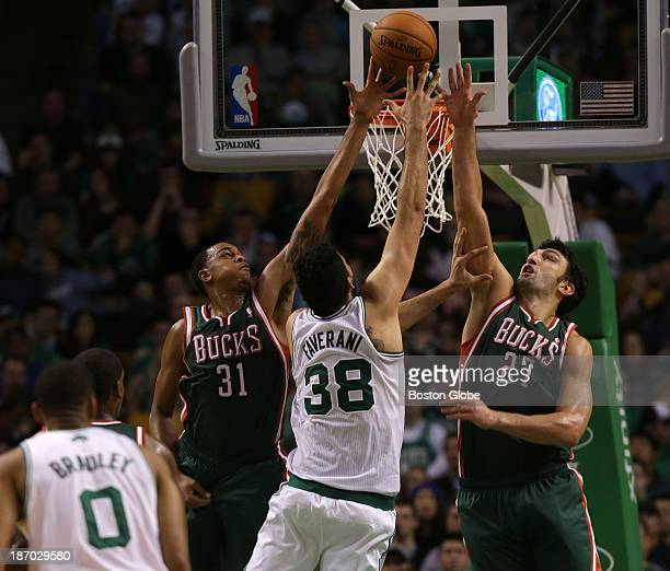 Milwaukee Bucks power forward John Henson and Milwaukee Bucks center Zaza Pachulia defends as Boston Celtics center Vitor Faverani goes up for a shot...