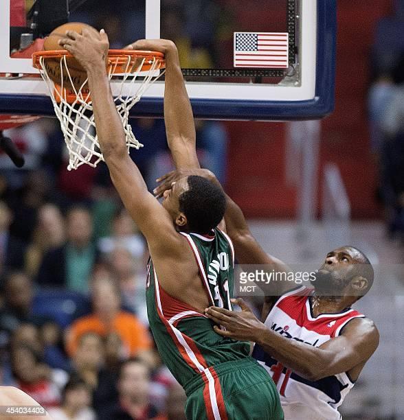Milwaukee Bucks power forward John Henson slam dunks on Washington Wizards small forward Chris Singleton during the second half of their game played...