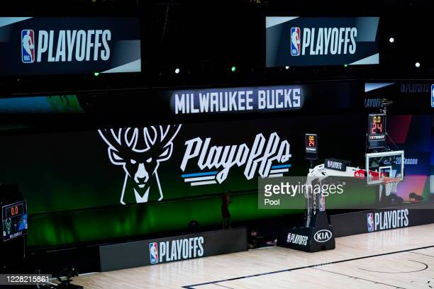 Milwaukee Bucks signage is displayed on screens beside an empty court at the scheduled start of the first half of game five against the Orlando Magic...