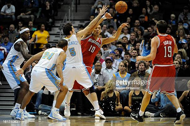 Milwaukee Bucks small forward Carlos Delfino passes the ball to point guard Beno Udrih as Denver Nuggets shooting guard Rudy Fernandez defends during...