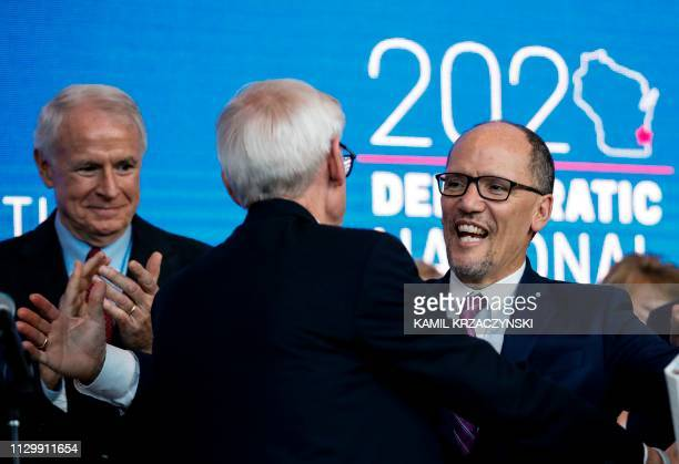 Milwaukee Mayor Tom Barrett looks on as Wisconsin Governor Tony Evers and Chair of the Democratic National Committee Tom Perez hug during a press...