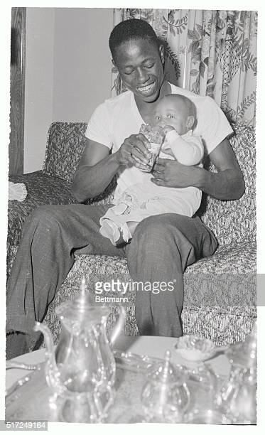 Milwaukee slugger Hank Aaron waiting to tackle the Yanks in the World Series relaxes at his home here September 26th with his son Hank Jr Aaron hits...