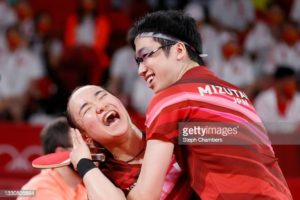 Mima Ito and Jun Mizutani of Team Japan embrace after winning their Mixed Doubles Gold Medal match on day three of the Tokyo 2020 Olympic Games at...