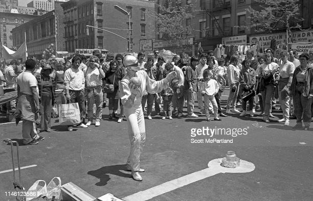 A mime performs for a crowd in the middle of 9th Avenue in Hell's Kitchen New York New York May 14 1988