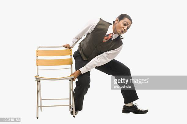 mime trying to remove a chair - indian removal act stock photos and pictures