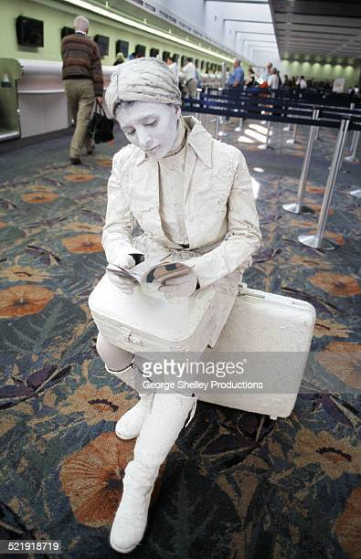 Mime waits motionless in an airport