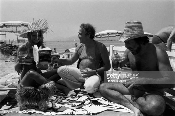 Mimi Coutelier et Jean Yanne boivent un verre sur une plage lors du Festival de Cannes le 14 mai 1979 France