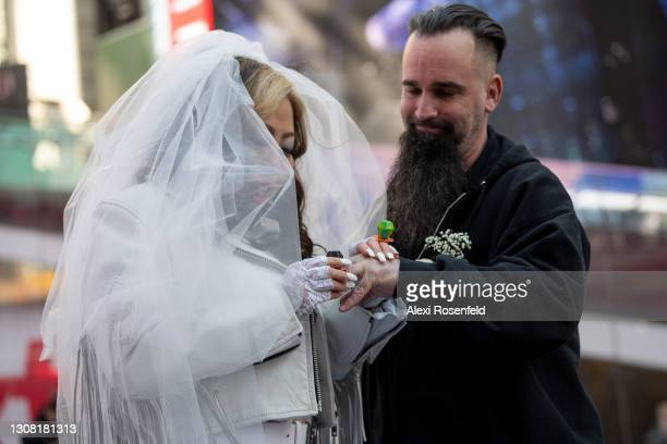 """Mimi Kim and Ken Lascar, from Hackensack, NJ, exchange candy """"ring-pop"""" rings while eloping on the first day of spring in Times Square on March 20,..."""