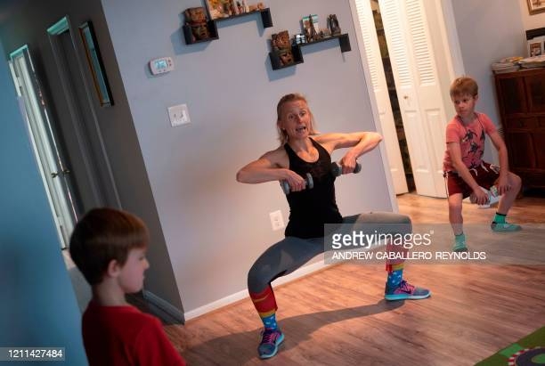 TOPSHOT Mimicked by her son Daniel Paulina Mansz a group fitness instructor records a workout session for her clients while her other son Javier...