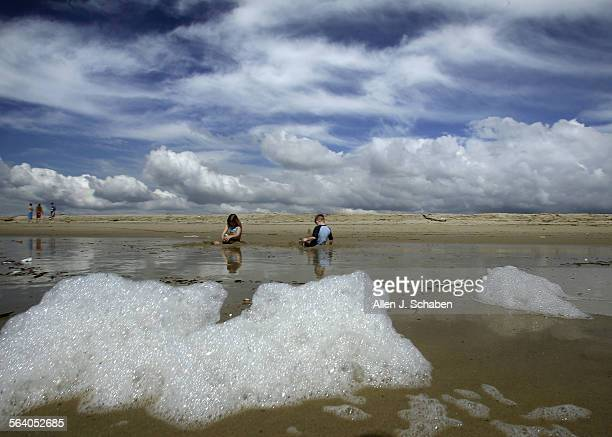 Mimicking the shape of clouds sea foam washes ashore as vacationers Skylar Cannon left and brother Zach Cannon of Seattle WA enjoy a break from the...