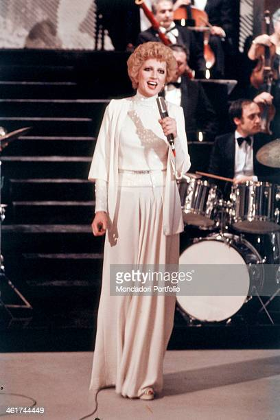 Mina born Mina Anna Maria Mazzini performs singing a song accompanied by an orchestra on the stage of a TV studio she wears a white suit with a long...