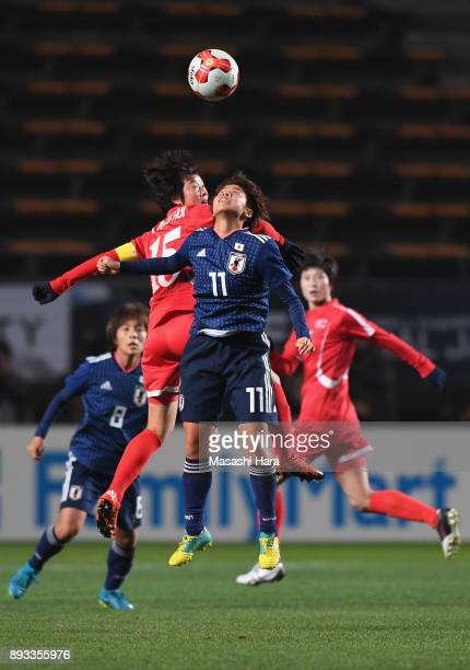 Mina Tanaka of Japan and Kim Nam Hui of North Korea compete for the ball during the EAFF E1 Women's Football Championship between Japan and North...