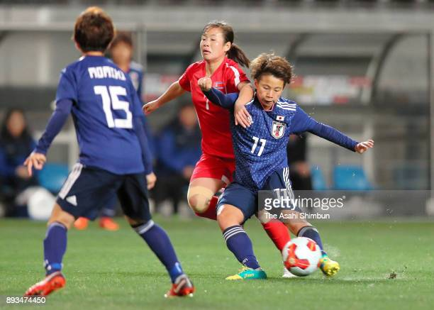 Mina Tanaka of Japan and Kim Un Hwa of North Korea compete for the ball during the EAFF E1 Women's Football Championship between Japan and North...