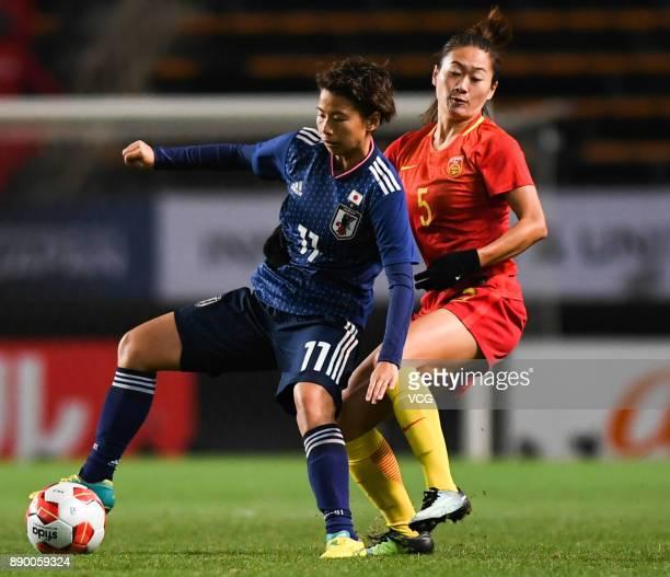 Mina Tanaka of Japan and Wu Haiyan of China compete for the ball during the EAFF E1 Women's Football Championship between Japan and China at Fukuda...