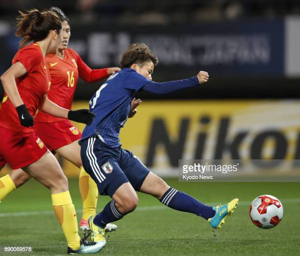 Mina Tanaka of Japan breaks free of China's defense to score during the first half of a women's match in the E1 Football Championship at Fukuda...