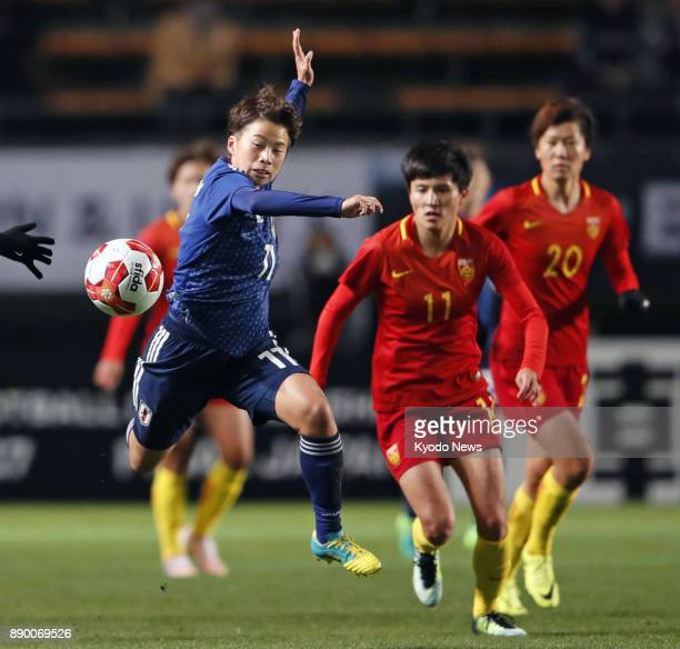 Mina Tanaka of Japan chases the ball under pressure from Wang Shanshan of China during the first half of a women's match in the E1 Football...