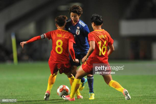 Mina Tanaka of Japan competes for the ball against Ma Jun and Han Peng of China during the EAFF E1 Women's Football Championship between Japan and...