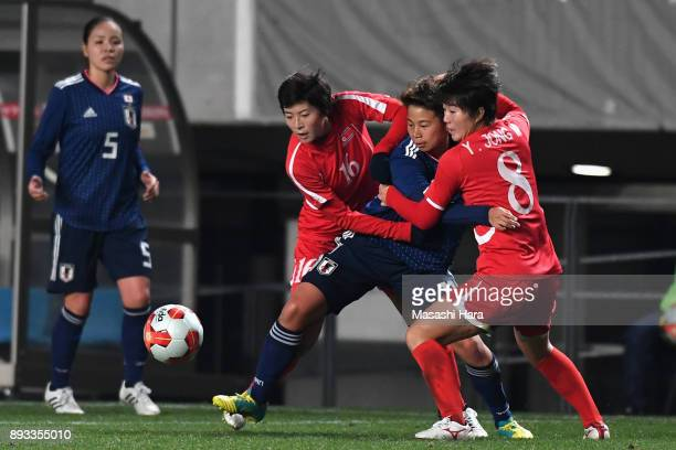 Mina Tanaka of Japan competes for the ball against Yu Jong Im and Kim Un Ha of North Korea during the EAFF E1 Women's Football Championship between...