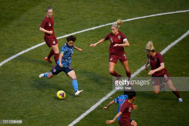 Mina Tanaka of Japan dribbles the ball as Steph Houghton and Millie Bright of England defend during the first half in the SheBelieves Cup at Red Bull...