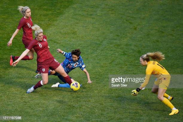 Mina Tanaka of Japan falls as Millie Bright Steph Houghton and Ellie Roebuck of England defend during the first half in the SheBelieves Cup at Red...
